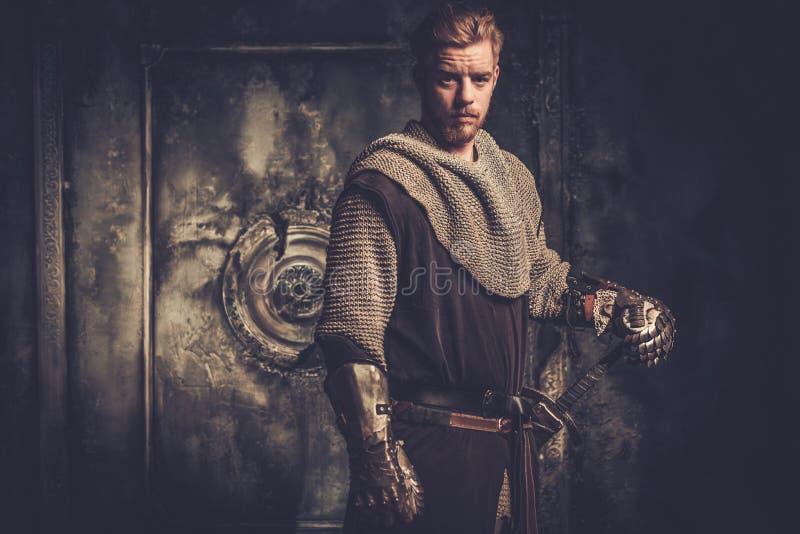 Ung medeltida riddare som poserar på mörk bakgrund arkivfoton