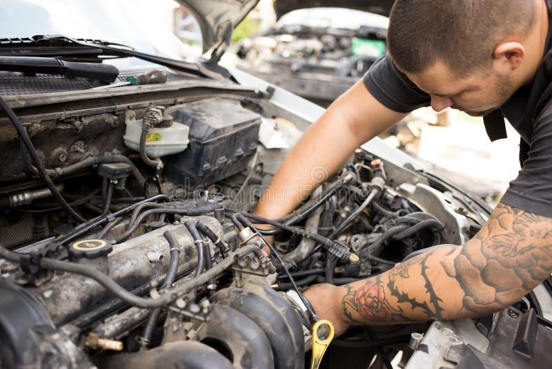Ung mekaniker som arbetar på en bil royaltyfri bild
