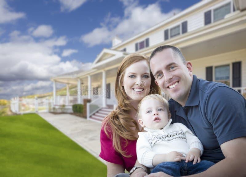 Ung militär familj framme av det härliga huset arkivfoto