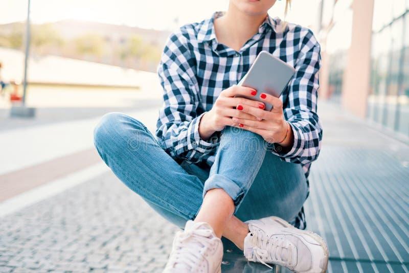 Ung millennial flicka som pratar och använder den smarta telefonen i staden royaltyfri bild