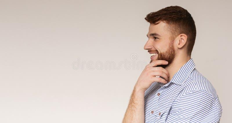 Ung millennial man som bort ser på utrymme och att le för kopia arkivbilder