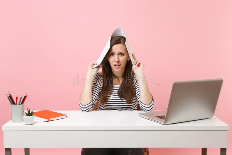 Ung missbelåten kvinna som rymmer pappers- dokument nära huvudet som arbetar på projekt, medan sitta på kontoret med bärbara dato arkivfoton