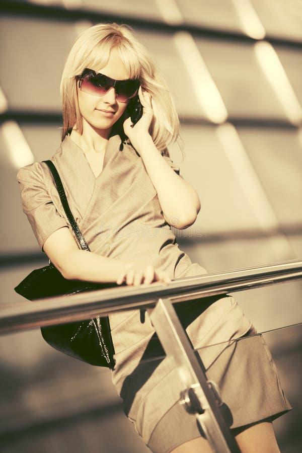 Ung modeaffärskvinna i solglasögon som talar på mobiltelefonen arkivbilder