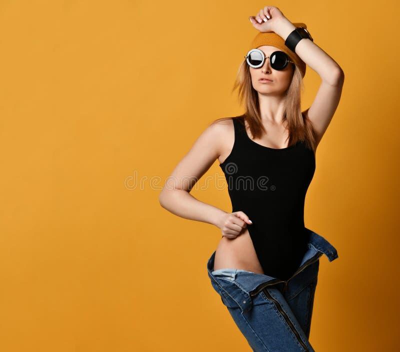 Ung modekvinna som bär knäppte upp jeansben och den svarta sexiga baddräkten på guling royaltyfri bild