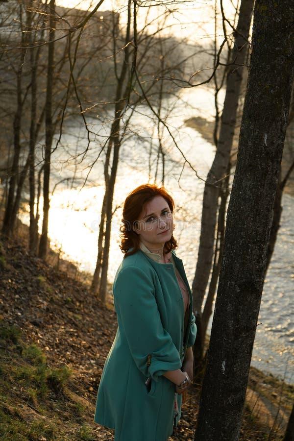 Ung modekvinna som kopplar av och tycker om solnedgång nära en flod i Bauska, Lettland, 2019 royaltyfri bild