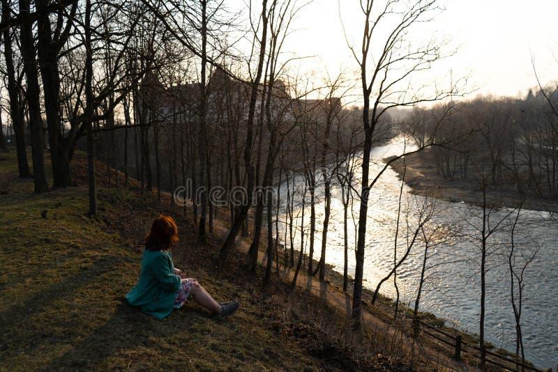 Ung modekvinna som kopplar av och tycker om solnedgång nära en flod i Bauska, Lettland, 2019 arkivfoto