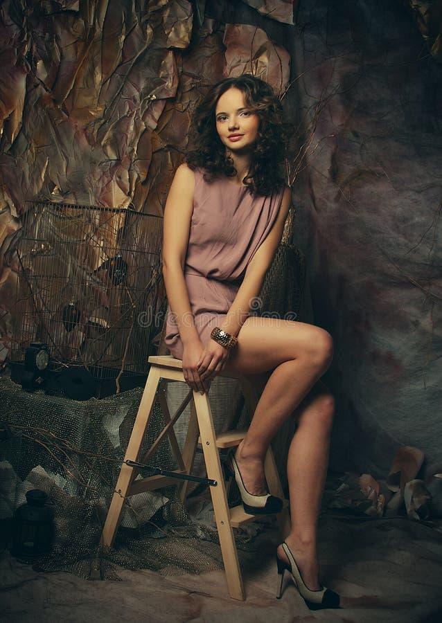 Ung modemodell med idérikt sminksammanträde på en stol in royaltyfri bild