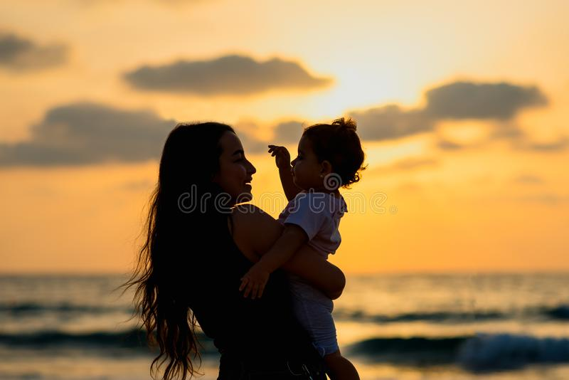 Ung moder för konturer med dottern som spelar och ler på stranden på solnedgången Lyckligt familj- och loppbegrepp arkivfoto