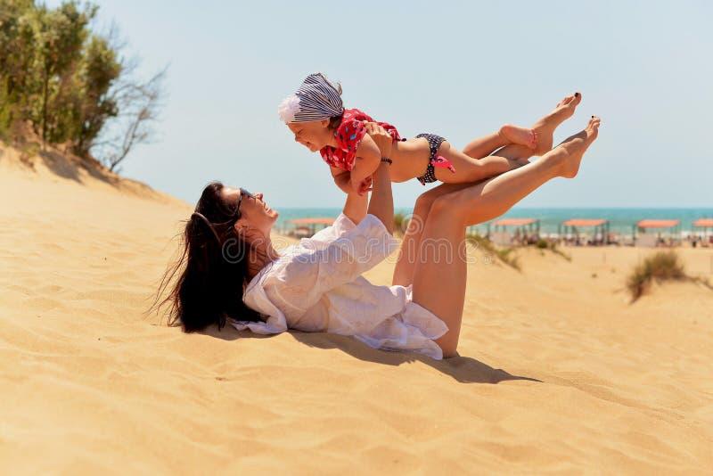 Ung moder med den lilla dottern som har gyckel på den sandiga stranden royaltyfri fotografi