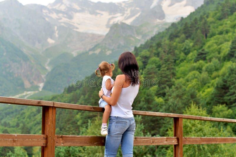 Ung moder med lite dottern som vilar i natur i bergen arkivfoton