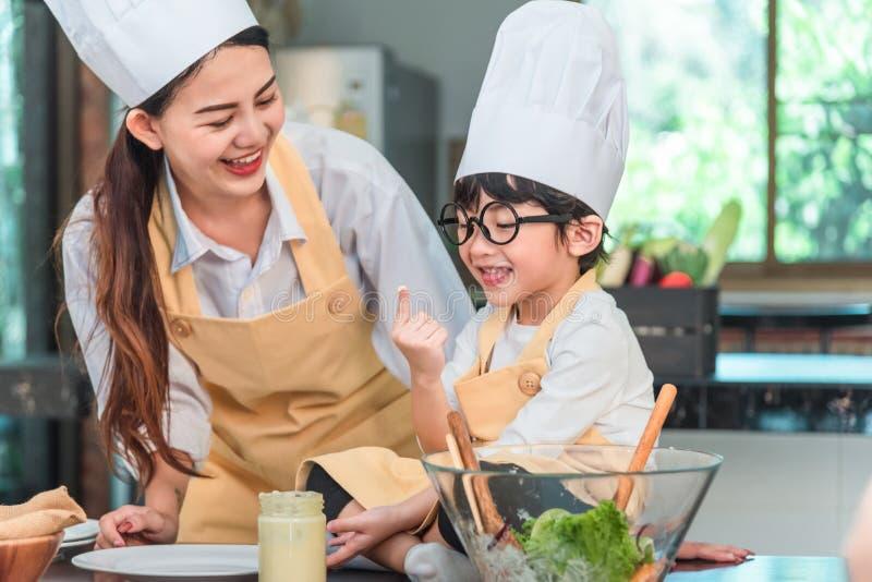 Ung moder och dotter som tillsammans lagar mat mål royaltyfri foto