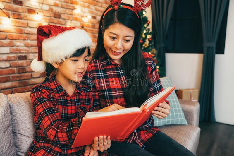 Ung moder och gullig flickaläsningsagobok royaltyfri fotografi