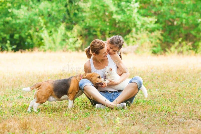Ung moder och hennes dotter som spelar med deras katt och hund fotografering för bildbyråer
