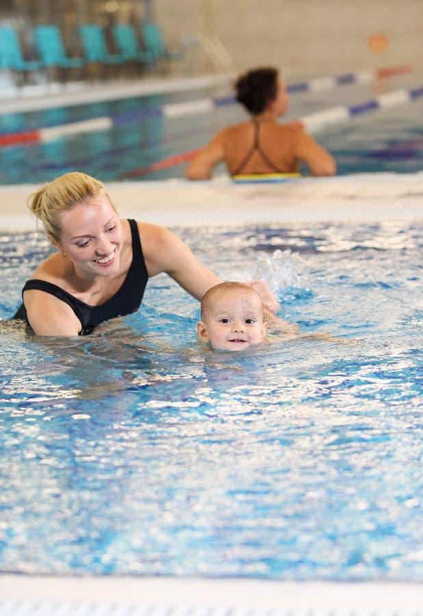 Ung moder och liten son i en simbassäng arkivbild
