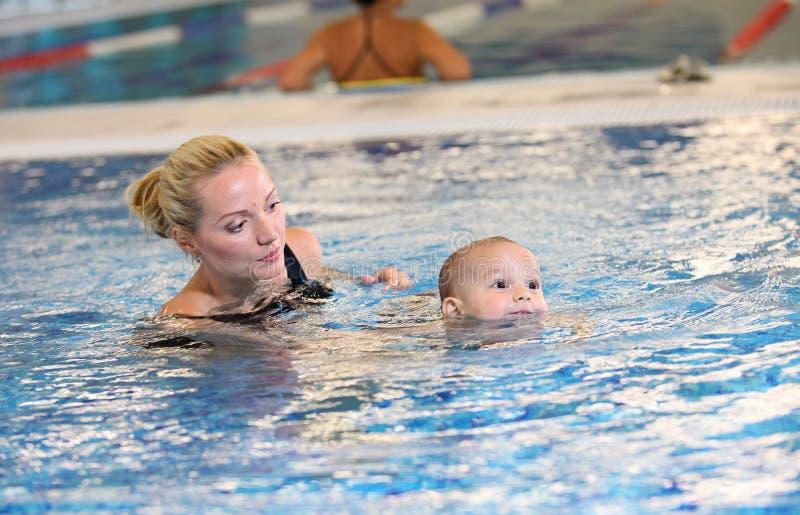 Ung moder och liten son i en simbassäng arkivbilder