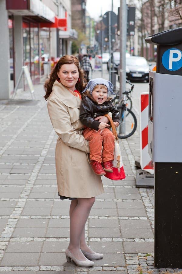 Ung moder- och litet barnpojke på stadsgatan royaltyfria foton