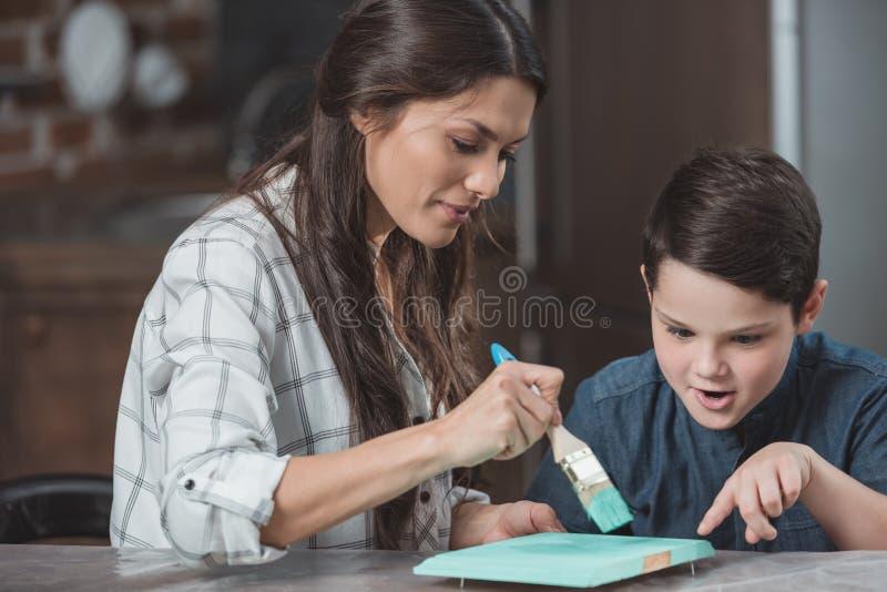 Ung moder som hjälper den lilla sonen att måla en del av royaltyfria bilder