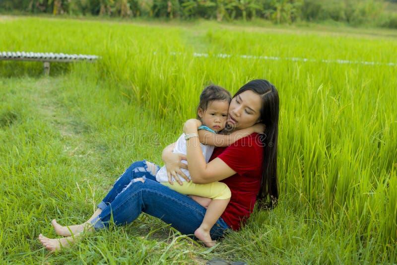 Ung moder som kramar och lugnar en skriande liten dotter, en asiatisk moder som f?rs?ker att tr?sta och lugna ner hennes skriande royaltyfri bild