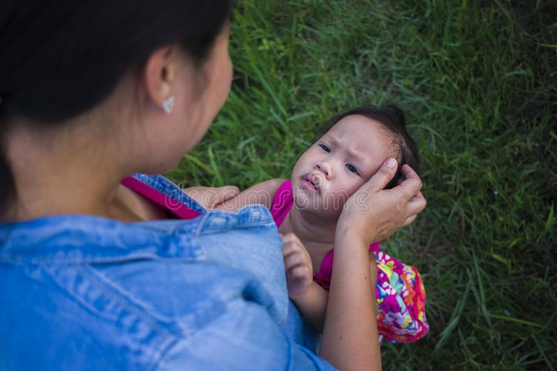 Ung moder som kramar och lugnar en skriande liten dotter, en asiatisk moder som f?rs?ker att tr?sta och lugna ner hennes skriande fotografering för bildbyråer