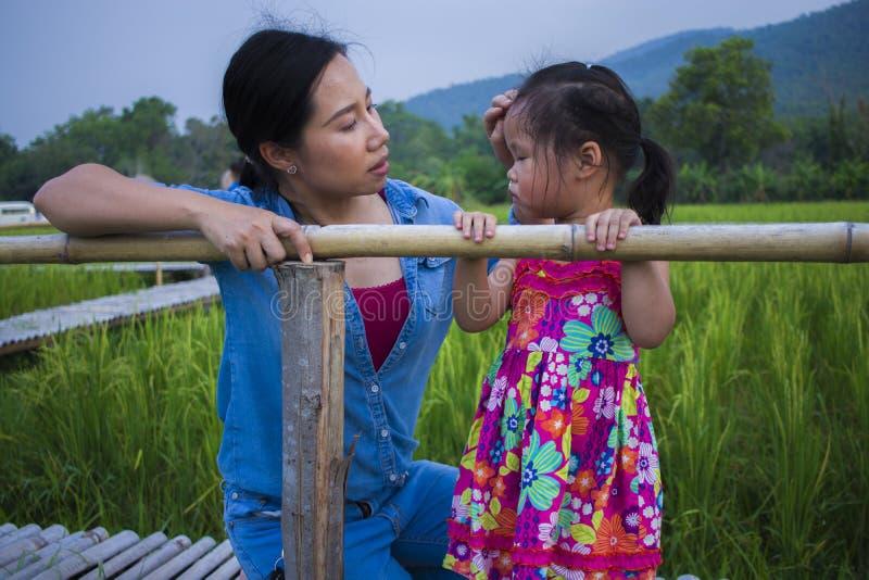 Ung moder som kramar och lugnar en skriande liten dotter, en asiatisk moder som f?rs?ker att tr?sta och lugna ner hennes skriande arkivfoton
