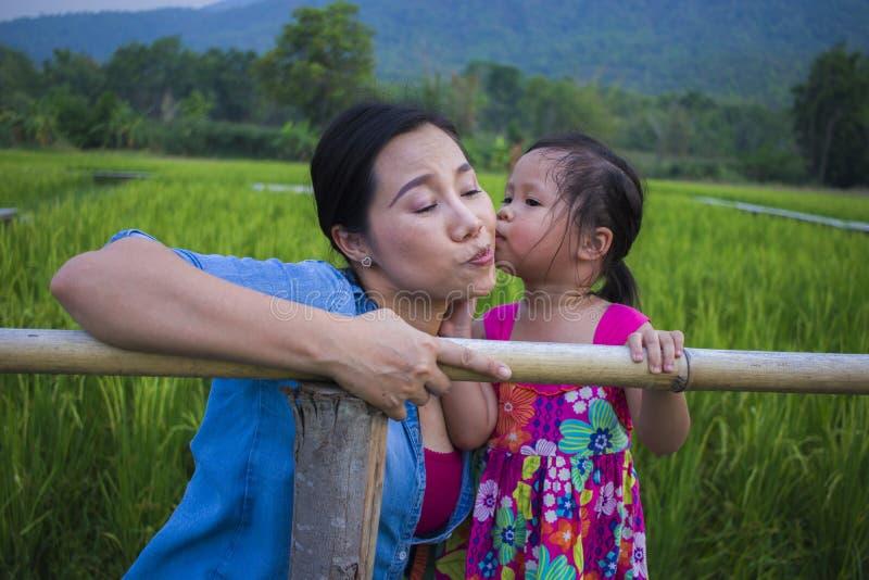 Ung moder som kramar och lugnar en skriande liten dotter, en asiatisk moder som f?rs?ker att tr?sta och lugna ner hennes skriande arkivbilder