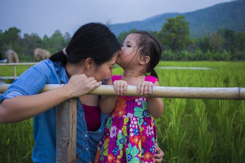 Ung moder som kramar och lugnar en skriande liten dotter, en asiatisk moder som f?rs?ker att tr?sta och lugna ner hennes skriande royaltyfri foto