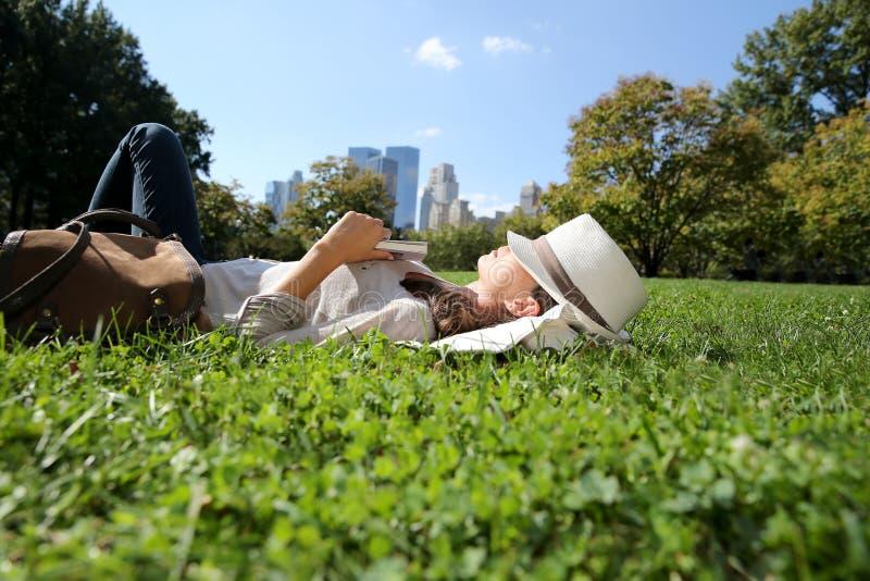 Ung moderiktig kvinna som ligger i gräs arkivbilder