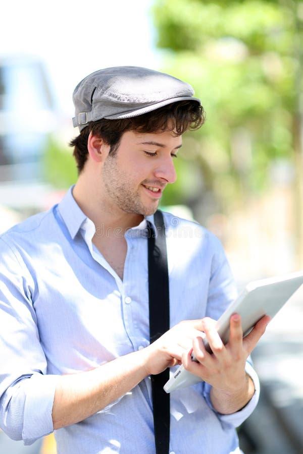 Ung moderiktig man som använder minnestavlan i gatorna royaltyfri fotografi