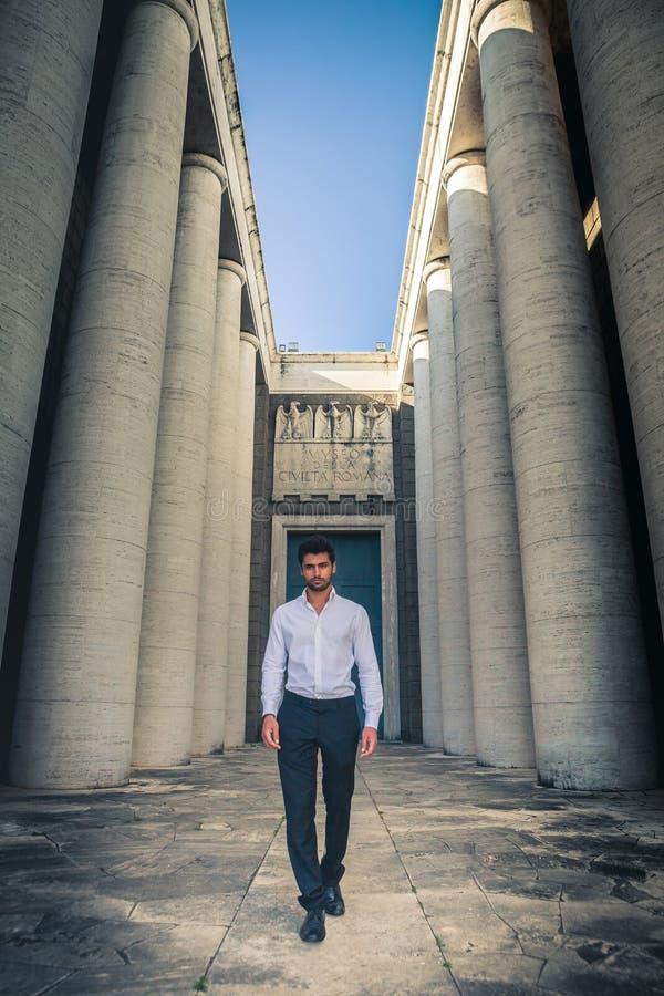 Ung moderiktig man som går till och med de forntida kolonnerna av en historisk byggnad fotografering för bildbyråer