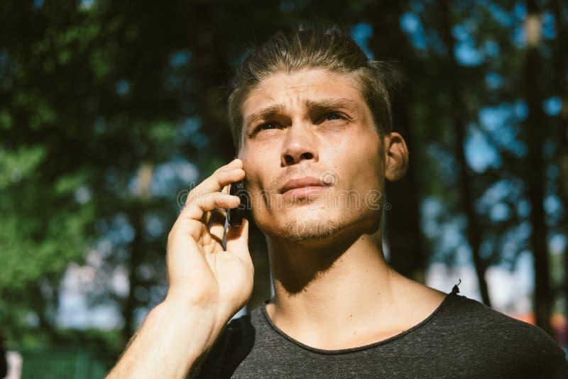 Ung moderiktig man som talar på telefonen i parkera arkivbild