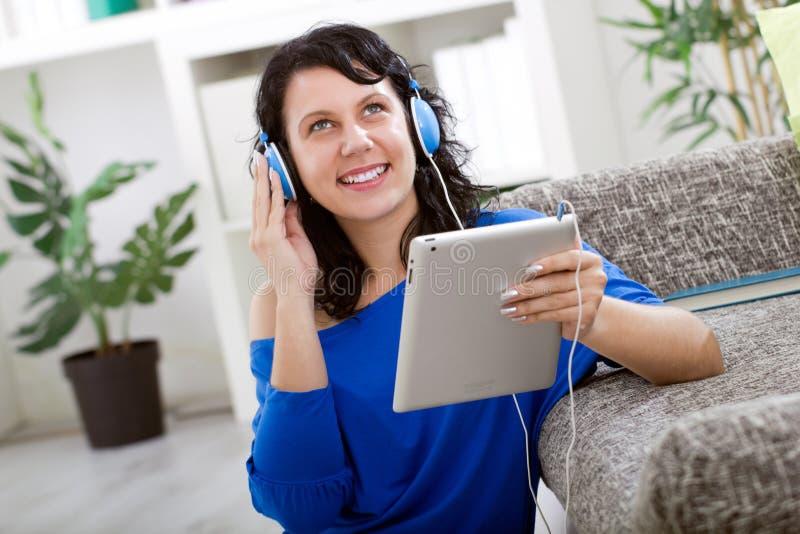 Ung modern flicka som lyssnar till musik med den elektroniska minnestavlan arkivbild