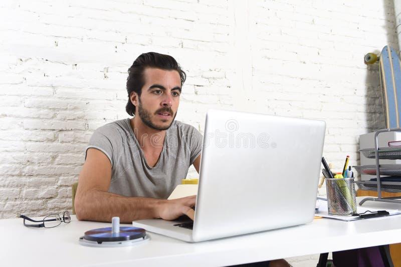 Ung modern hipsterstilstudent eller affärsman som arbetar med det hemmastadda kontoret för bärbar datordator arkivbilder