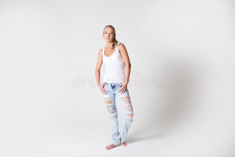 Ung modern le kvinna i jeans och en T-tröja på en grå bakgrund fotografering för bildbyråer