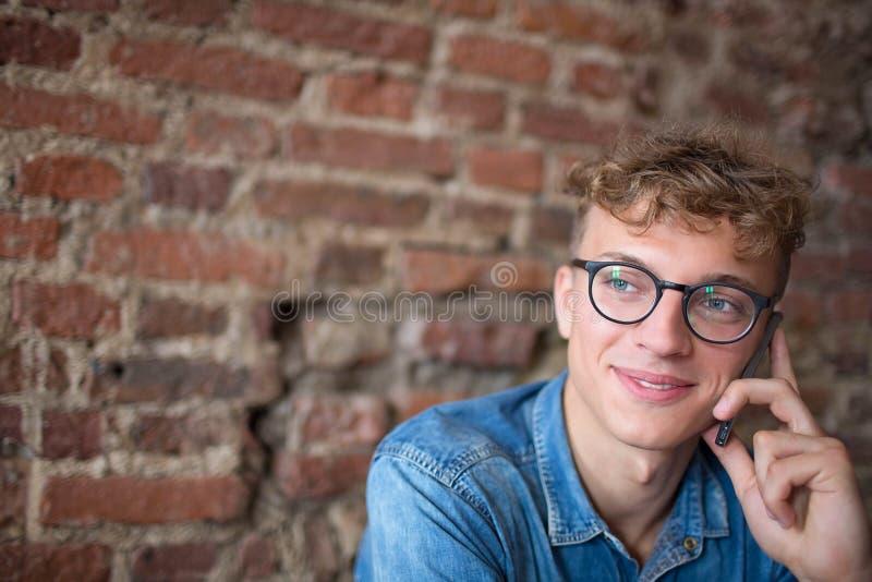 Ung modern stilfull affärsman i exponeringsglas som har celltelefonkonversation royaltyfria foton
