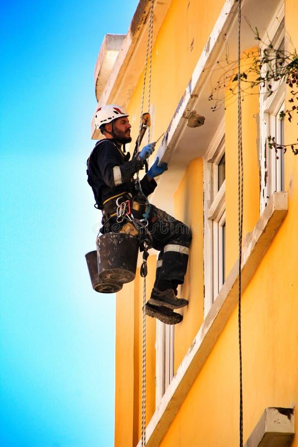Ung murareklättrare som gör reparationsarbete i en fasad av Lissabon royaltyfri foto