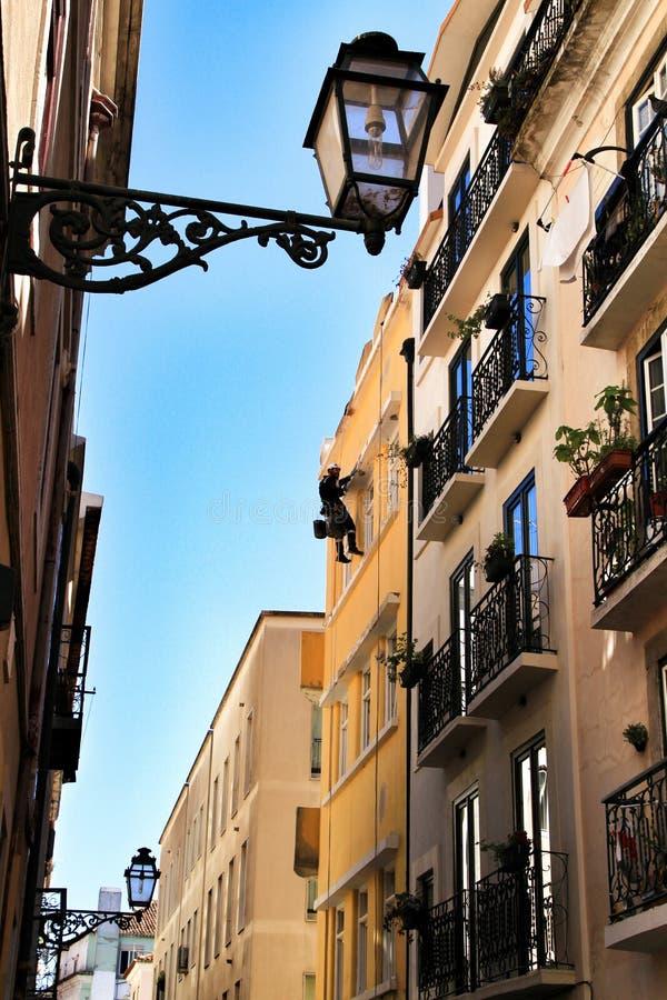 Ung murareklättrare som gör reparationsarbete i en fasad av Lissabon royaltyfria foton