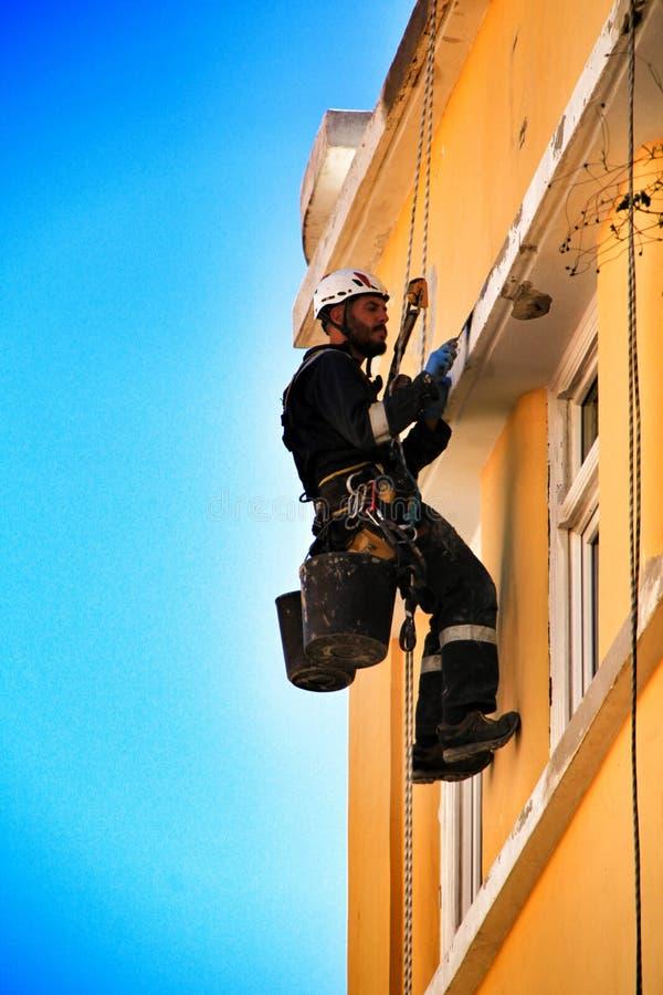 Ung murarekl?ttrare som g?r reparationsarbete i en fasad av Lissabon arkivbilder