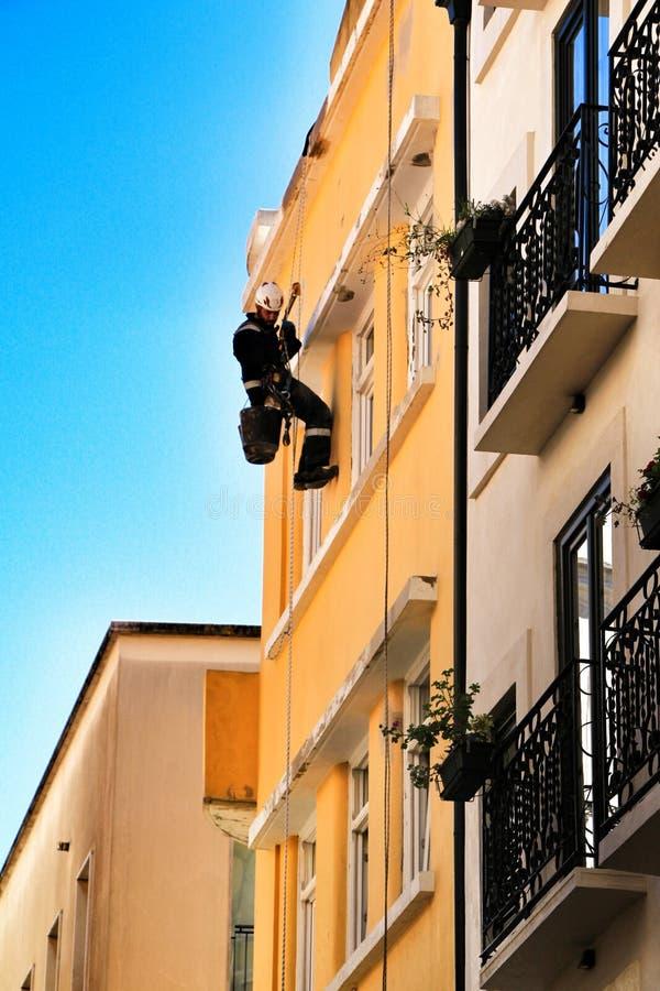 Ung murarekl?ttrare som g?r reparationsarbete i en fasad av Lissabon arkivfoton