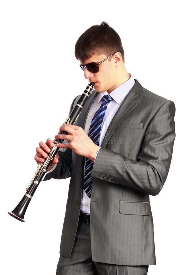 Ung musiker med solglasögon som spelar klarinetten royaltyfri bild
