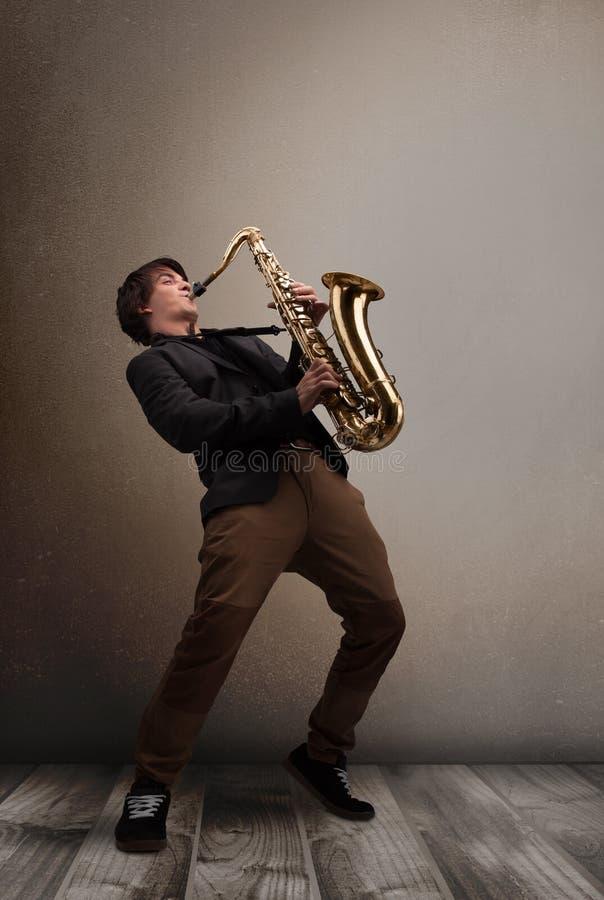 Ung musiker som spelar på saxofonen royaltyfri bild