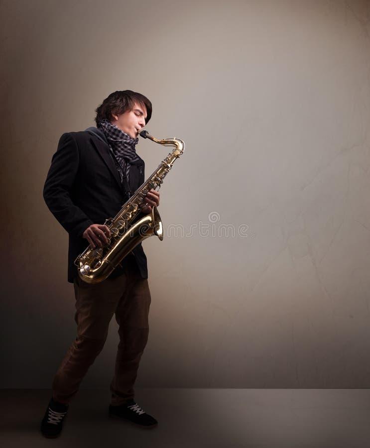 Ung musiker som spelar på saxofonen arkivbild