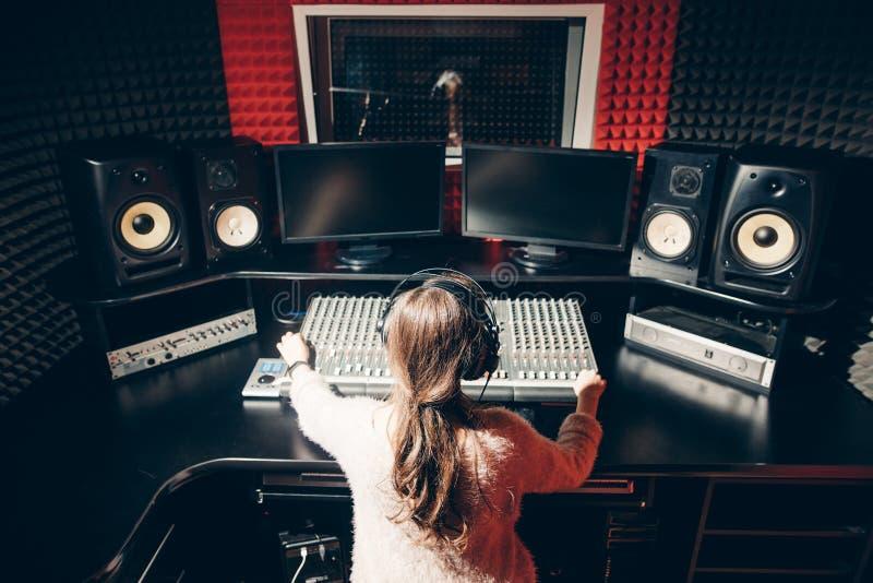 Ung musikoperatör som kontrollerar ljudet i studion arkivbilder