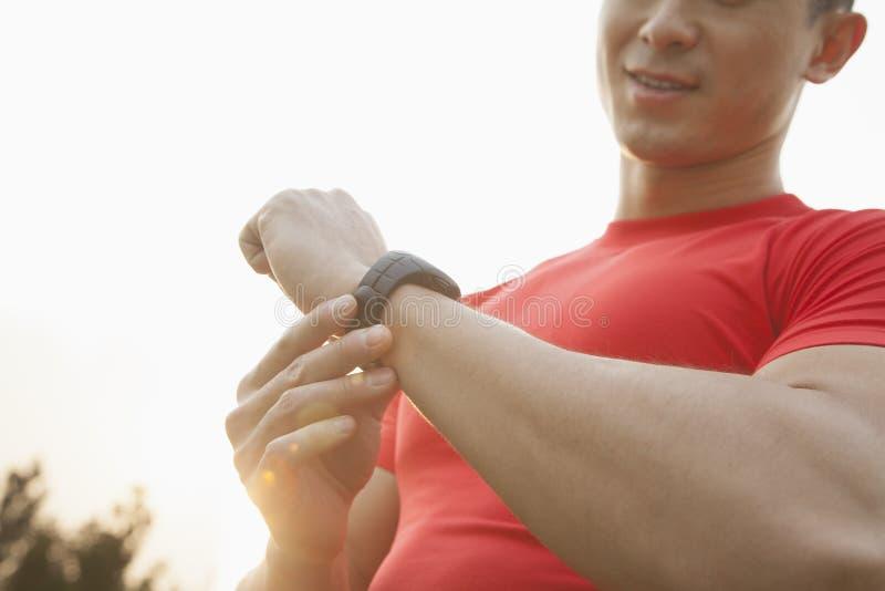 Ung muskulös man med den röda skjortan som ner ser och kontrollerar hans klocka, utomhus i Peking arkivbilder