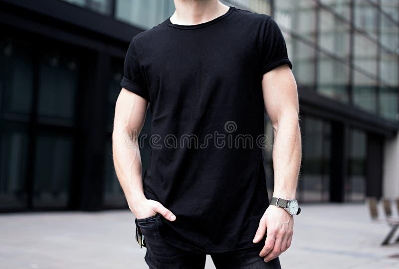 Ung muskulös man som bär den svarta tshirten och jeans som poserar i mitt av den moderna staden suddighet bakgrund Hotizontal mod royaltyfri foto