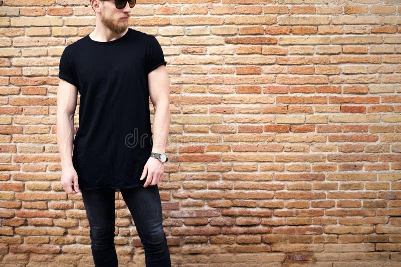 Ung muskulös man som bär den svarta tshirten, solglasögon och jeans som utanför poserar Töm den bruna grungetegelstenväggen på fotografering för bildbyråer