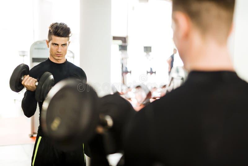 Ung muskulös man som utarbetar i en idrottshall och lyftande vikter arkivfoton