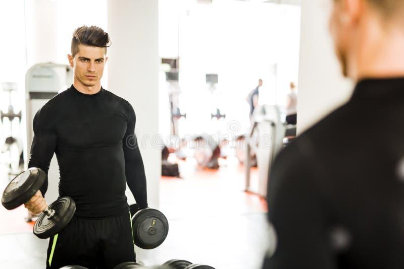 Ung muskulös man som utarbetar i en idrottshall och lyftande vikter royaltyfria foton