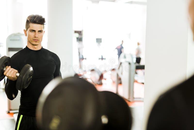 Ung muskulös man som utarbetar i en idrottshall och lyftande vikter arkivbild
