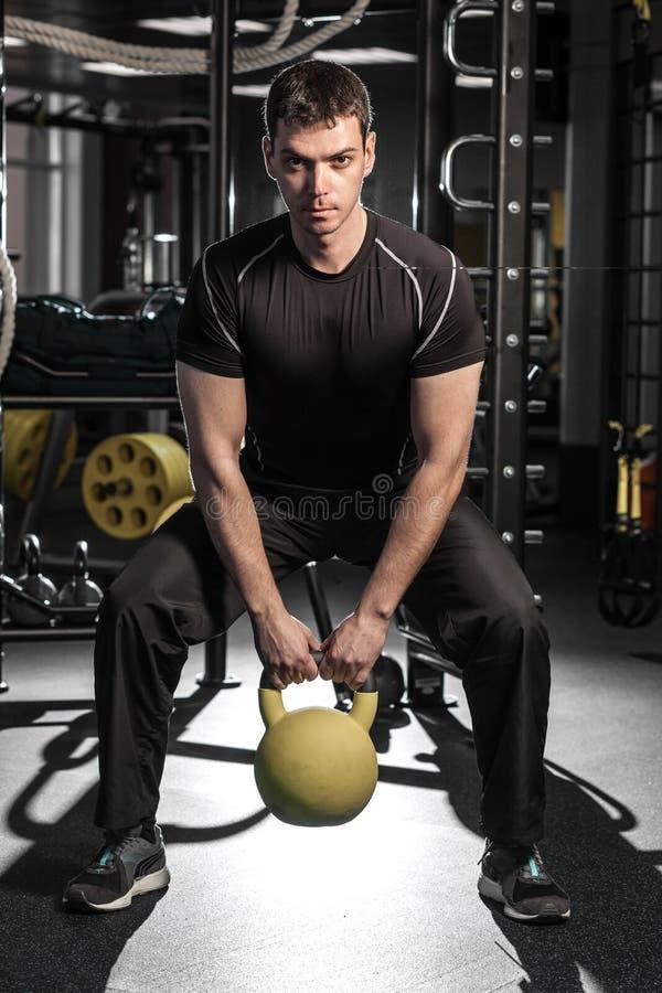 Ung muskulös man som utarbetar i idrottshallen royaltyfria foton