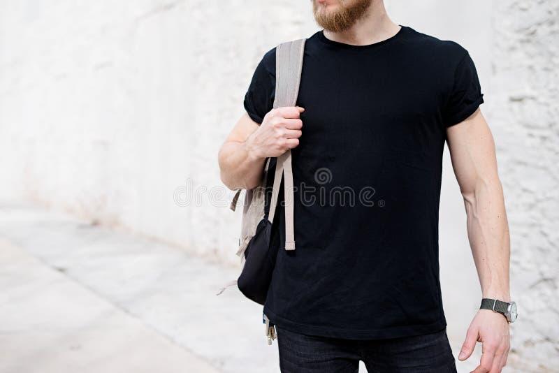 Ung muskulös skäggig man som bär den svarta tshirten och ryggsäcken som utanför poserar Tom vit betongvägg på bakgrunden arkivfoton